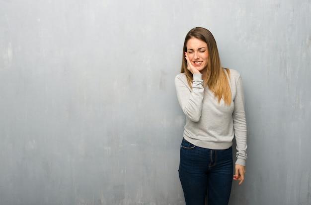 Młoda kobieta na textured ścianie z toothache