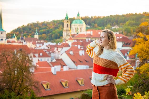 Młoda kobieta na tle czerwonego dachu starego miasta w pradze w czechach
