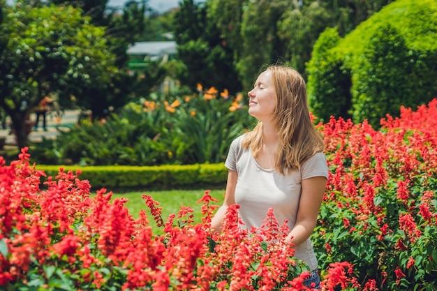 Młoda kobieta na tle czerwonych kwiatów szałwii splendens kwitnących w ogrodzie