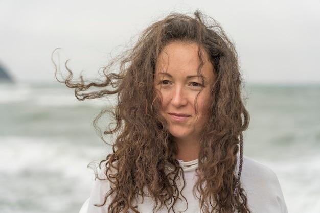Młoda kobieta na tle morza, machając głową na bok i łopocze włosami na wietrze. urocza brunetka dziewczyna na wybrzeżu morza. piękna kobieta cieszy się wiatrem, poczuciem wolności