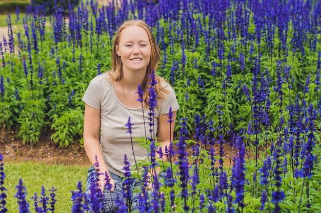 Młoda kobieta na tle niebieskich kwiatów szałwii farinacea kwitnących w ogrodzie