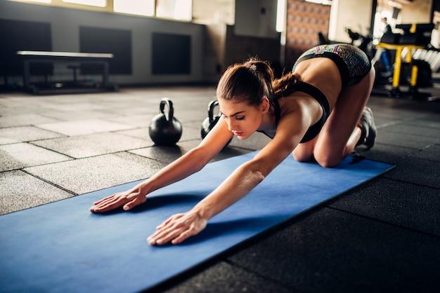 Młoda kobieta na treningu fitness w klubie sportowym. lekkoatletka, trening na siłowni
