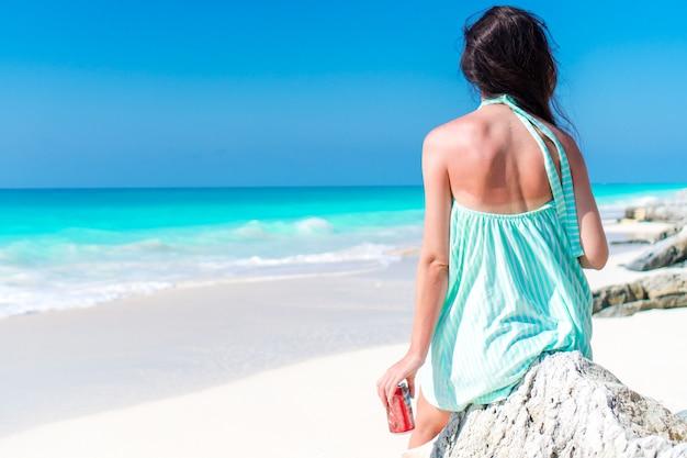 Młoda kobieta na tropikalnej plaży z jej napojami