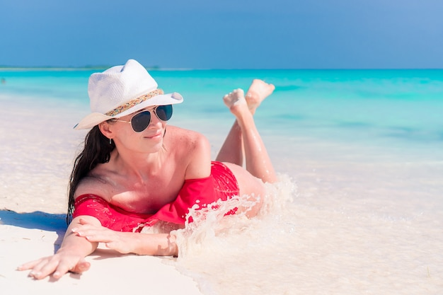 Młoda kobieta na tropikalnej plaży z kapeluszem