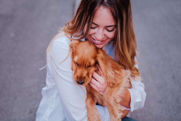 Młoda kobieta na ulicy trzymając ze swoim uroczym psem kokera na ramieniu. styl życia na zewnątrz ze zwierzętami