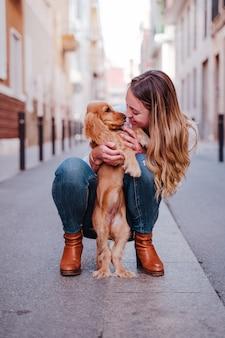 Młoda kobieta na ulicy tulenie jej cute cocker dog. styl życia na zewnątrz ze zwierzętami