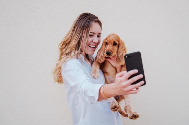 Młoda kobieta na ulicy z psem cocker fotografowanie telefonem komórkowym. styl życia na zewnątrz ze zwierzętami