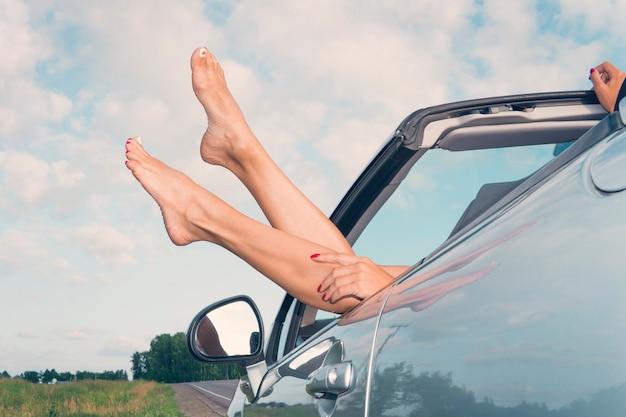 Młoda kobieta na wakacjach. szczęśliwa dziewczyna w kabriolecie na tle nieba. lato. wycieczki krajoznawcze. weekend