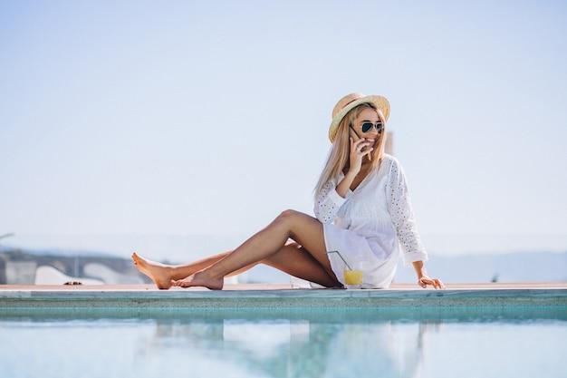 Młoda kobieta na wakacje przy basenie przy użyciu telefonu