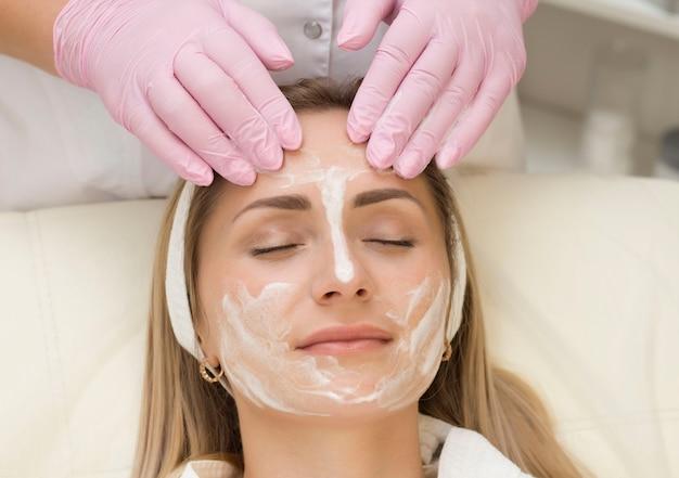 Młoda kobieta na wizycie u kosmetologa nakłada krem na twarz. zabieg upiększający