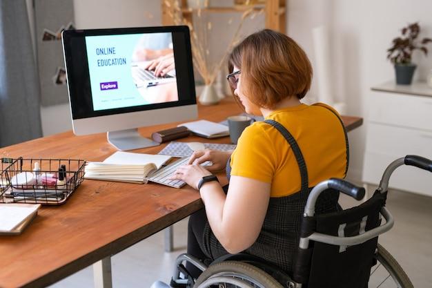 Młoda kobieta na wózku inwalidzkim naciskając klawisze na klawiaturze przed monitorem komputera podczas zdalnej lekcji w środowisku domowym