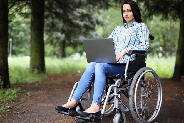Młoda kobieta na wózku inwalidzkim pracuje na laptopie w parku