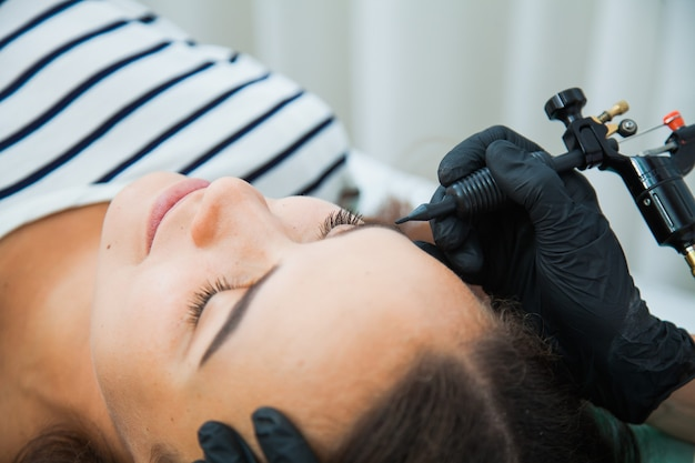 Młoda kobieta na zabiegu makijażu permanentnego, tatuuje brwi w naturalnym odcieniu. zbliżenie korekcji brwi.