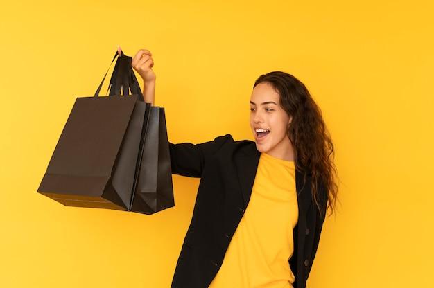 Młoda kobieta na zakupy z czarnymi torbami na kolorowym tle