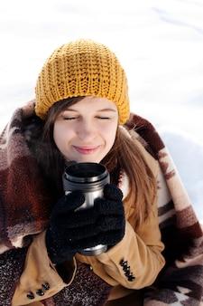 Młoda kobieta na zewnątrz picia gorącego napoju