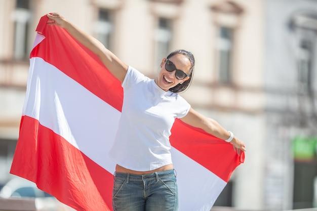 Młoda kobieta na zewnątrz trzyma flagę austrii, uśmiechając się.