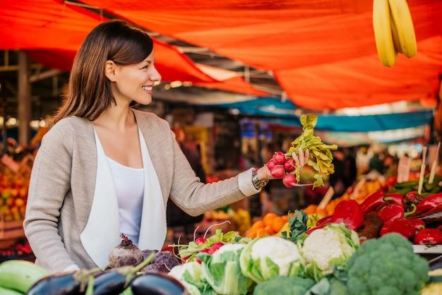 Młoda kobieta na zielonym rynku kupuje warzywa.