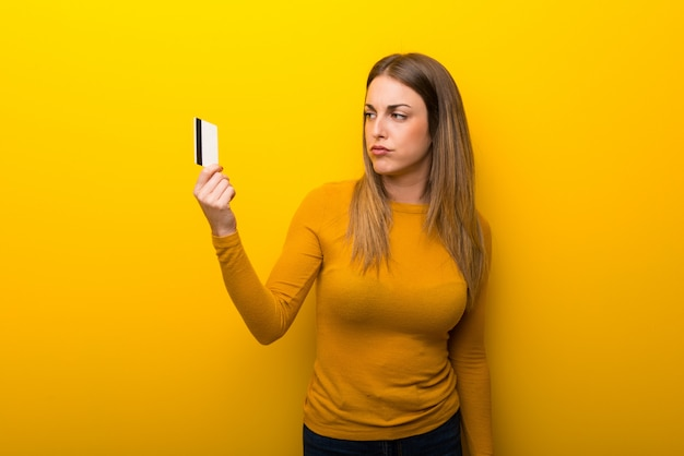 Młoda kobieta na żółtym tle bierze kredytową kartę bez pieniądze