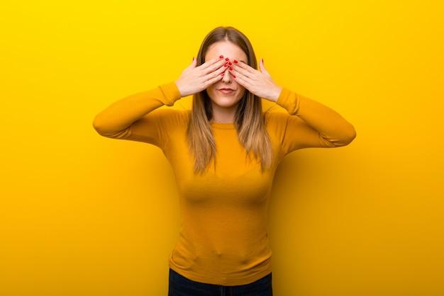 Młoda kobieta na żółtym tle zakrywa oczy rękami. zaskoczony, aby zobaczyć, co jest przed nami