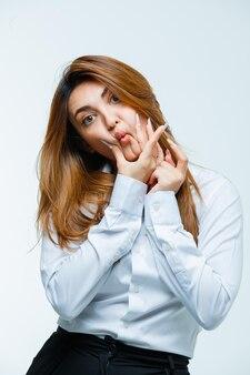 Młoda kobieta naciskając palce na policzki