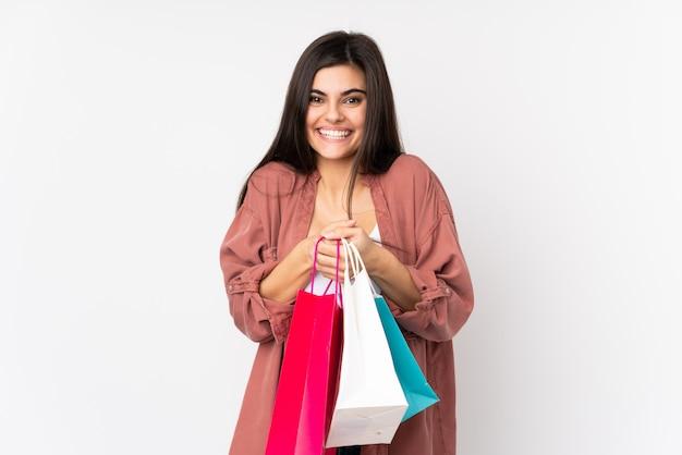 Młoda kobieta nad białej ściany gospodarstwa torby na zakupy i zaskoczony