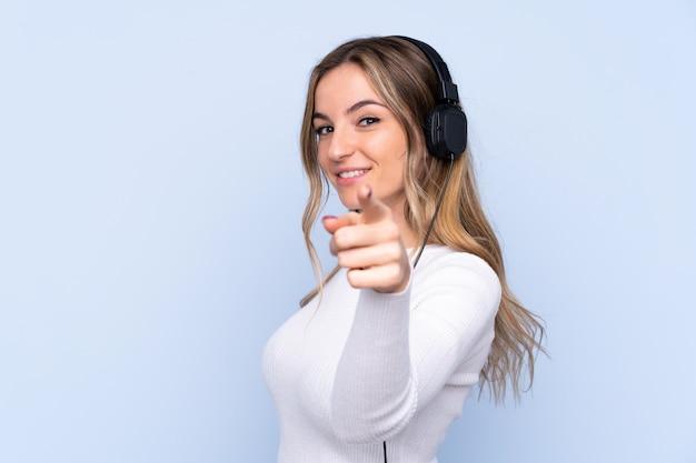 Młoda kobieta nad izolowane niebieską ścianą słuchania muzyki i wskazując na przód