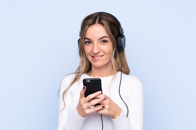 Młoda kobieta nad izolowane niebieską ścianą słuchania muzyki z przodu telefonu komórkowego i patrząc