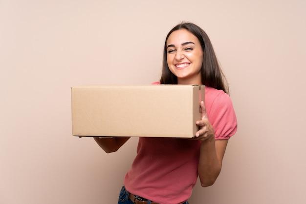 Młoda kobieta nad izolowanym gospodarstwa pudełko, aby przenieść go do innej witryny