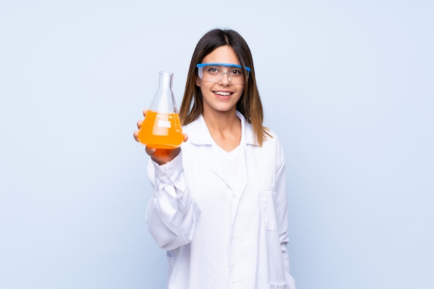 Młoda kobieta nad izolowanym niebieski z naukowej probówki