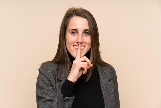 Młoda kobieta nad izolowanym ścianie robi gest ciszy