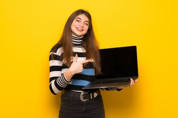 Młoda kobieta nad kolor żółty ścianą pokazuje laptop