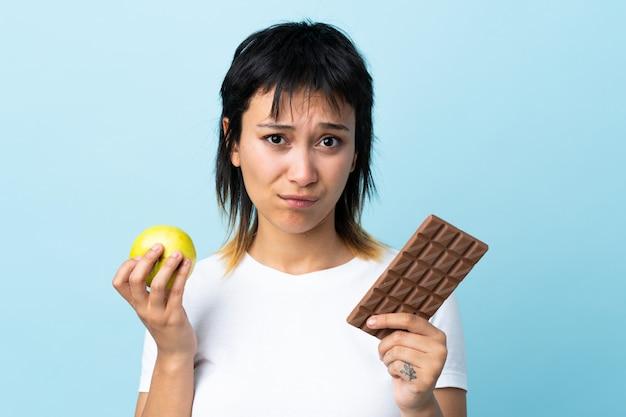 Młoda kobieta nad niebieską ścianą biorąc czekoladową tabletkę w jednej ręce i jabłko w drugiej