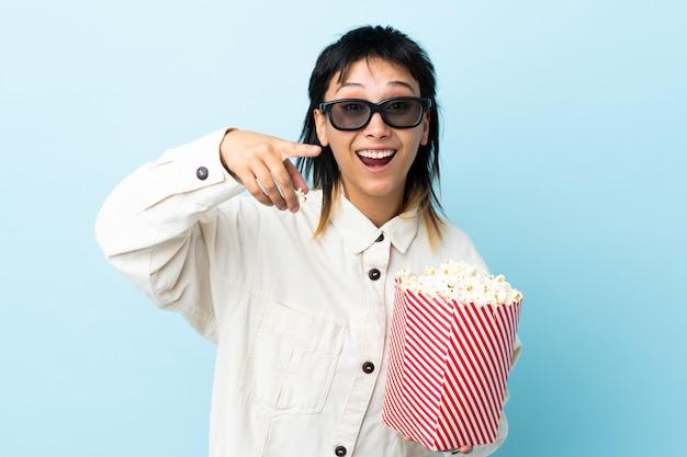 Młoda kobieta nad niebieską ścianą w okularach 3d i gospodarstwa duże wiadro popcorns, wskazując z przodu