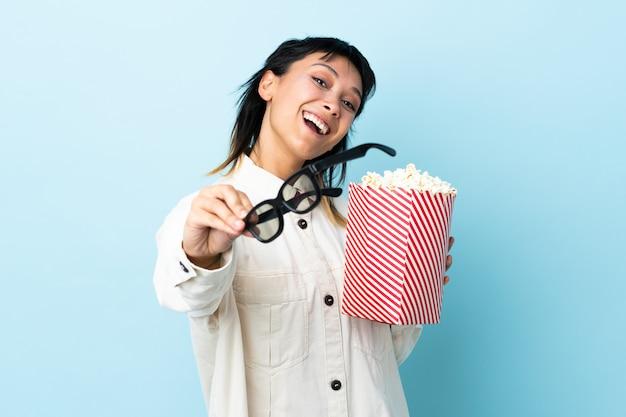 Młoda kobieta nad niebieską ścianą w okularach 3d i gospodarstwa duże wiadro popcorns