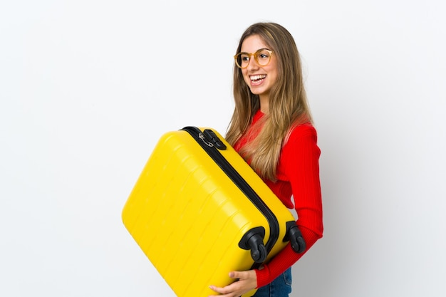 Młoda kobieta nad odosobnioną białą ścianą w wakacje z walizką podróżną