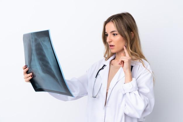 Młoda kobieta nad odosobnioną biel ścianą jest ubranym doktorską suknię i trzyma skan kości