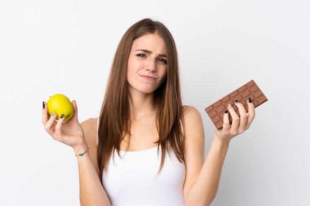 Młoda kobieta nad odosobnioną biel ścianą ma wątpliwości podczas gdy brać czekoladową pastylkę w jednej ręce i jabłko w drugiej