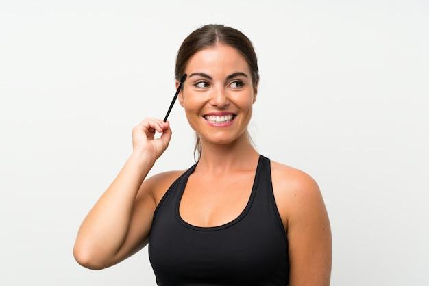 Młoda kobieta nad odosobnioną biel ścianą stosuje tusz do rzęs z kosmetyczną pośpiechu