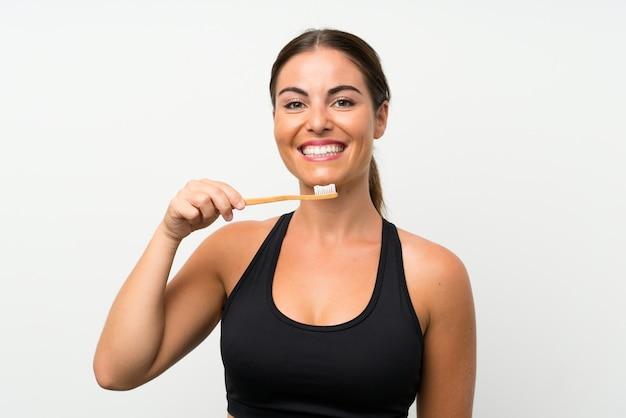 Młoda kobieta nad odosobnioną biel ścianą szczotkuje jej zęby