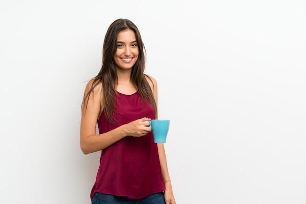 Młoda kobieta nad odosobnioną biel ścianą trzyma gorącą filiżankę kawy