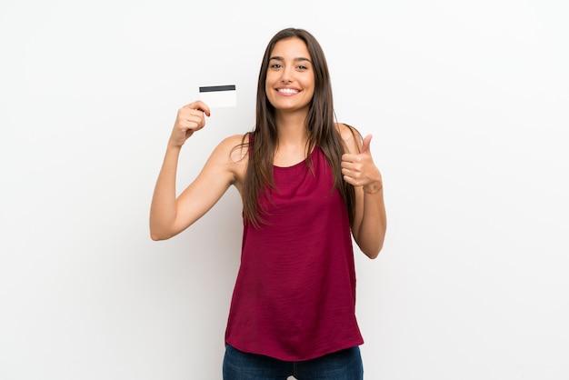 Młoda kobieta nad odosobnioną biel ścianą trzyma kartę kredytową