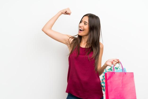 Młoda kobieta nad odosobnioną biel ścianą trzyma mnóstwo torba na zakupy