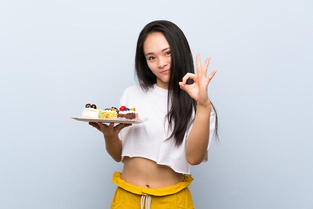Młoda kobieta nad odosobnioną biel ścianą trzyma puchar popcorns