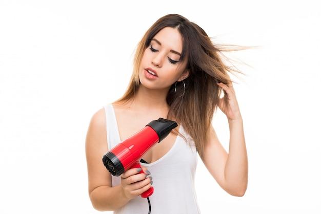Młoda kobieta nad odosobnioną biel ścianą z hairdryer