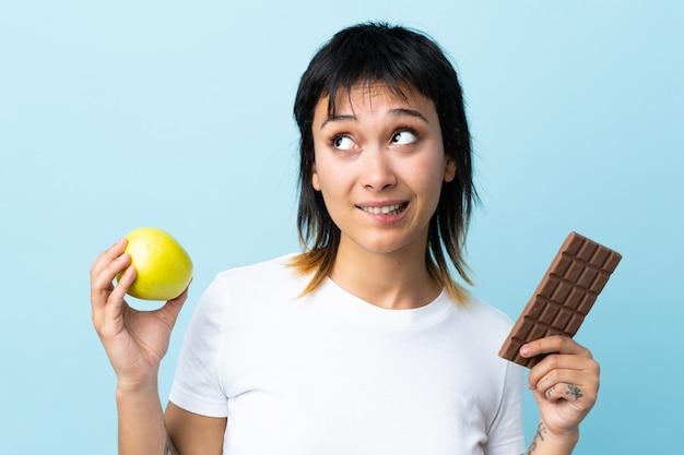 Młoda kobieta nad odosobnioną błękit przestrzenią ma wątpliwości podczas gdy brać czekoladową pastylkę w jednej ręce i jabłko w drugiej