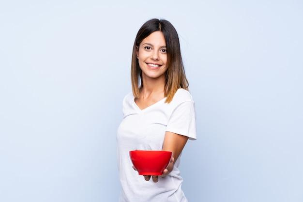 Młoda kobieta nad odosobnioną błękit ścianą trzyma puchar zboża