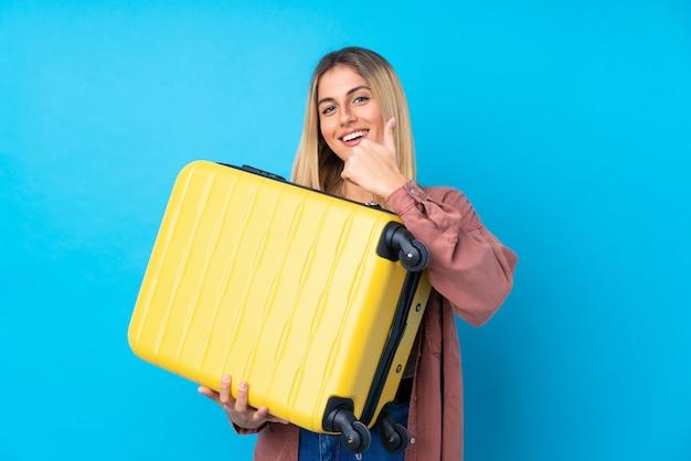 Młoda kobieta nad odosobnioną błękit ścianą w wakacje z podróży walizką z kciukiem up i