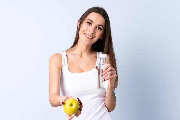 Młoda kobieta nad odosobnioną błękit ścianą z jabłkiem i butelką woda