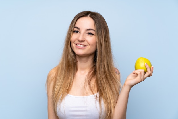 Młoda kobieta nad odosobnioną błękit ścianą z jabłkiem