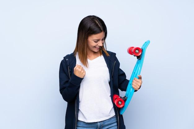 Młoda kobieta nad odosobnioną błękit ścianą z łyżwą i robić zwycięstwo gestowi
